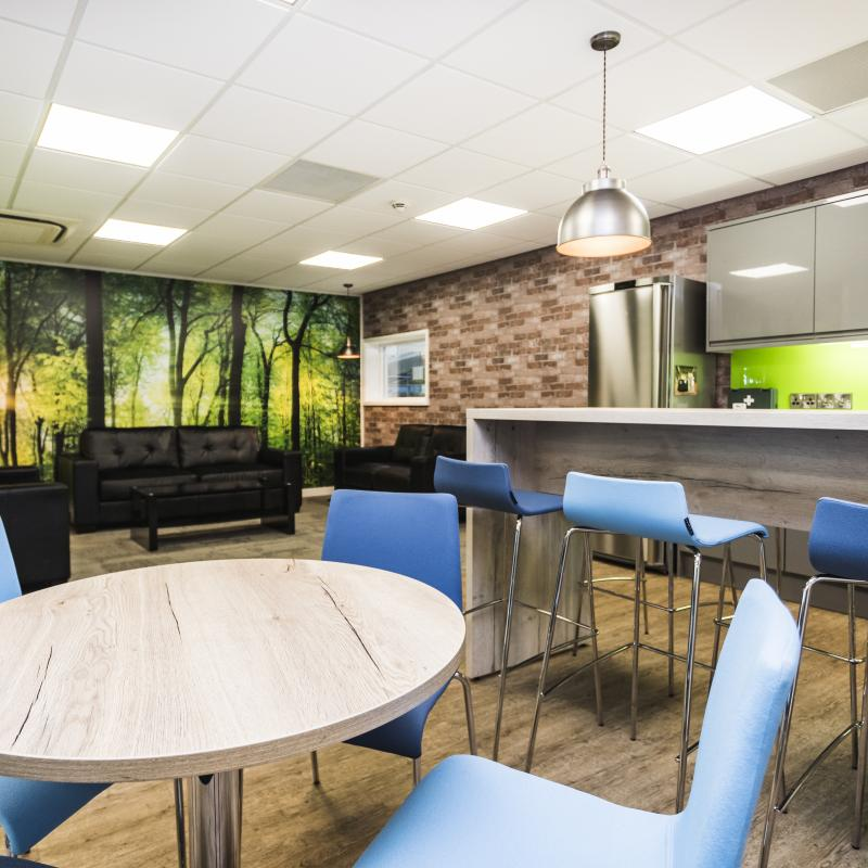 image of ground floor breakout / tea-point and lounge area with light oak coloured round table and high bench, two different blue chairs and stools in front of a straight section of gloss grey kitchen units. The units have a lime green splash-back. The lounge area has three  black leather sofas around black glass coffee table. Surrounding the sofas is a large forest scene image across the walls. There is feature pendant lighting above the high bench and in the lounge area corners.