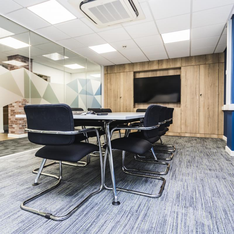 Image of ground floor meeting room showing white table, black and chrome chairs. Blue wall to right, end wall is a media panel in oak with large TV screen in the middle. Left wall of meeting room is glazed floor to ceiling with green and blue geometric shaped branding across central area.