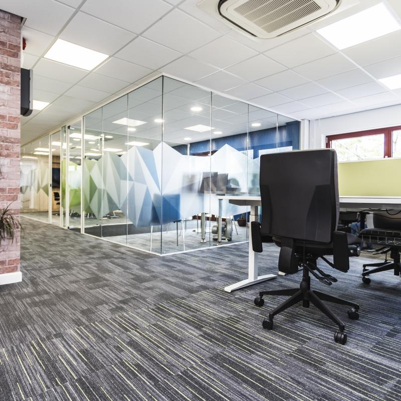 Image of ground floor desks looking towards the entrance foyer and meeting room. Black and grey carpet with green lines under desks and black lines for main corridor. Brick column with plant. Branding graphics on glazed walls.