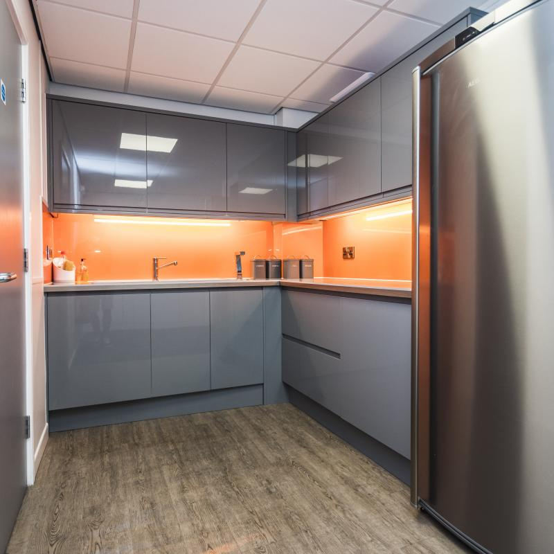 Image of 1st floor tea point showing grey gloss units with high gloss orange splash back. Pelmet lights on under wall units creating reflections on orange splash back, Wooden plank effect flooring and stainless steel fridge.