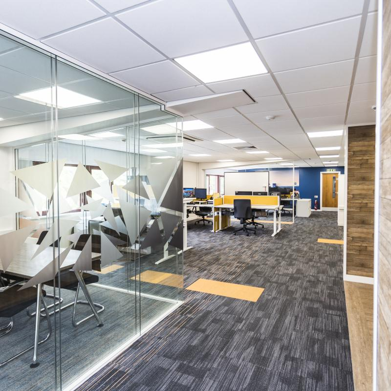 Image of bright new 1st floor open plan office with MD's glazed office on left showing new black and orange branding. Carpet is black and grey with small orange lines and inset orange tiles. Desks are white with orange screens and grey chairs.