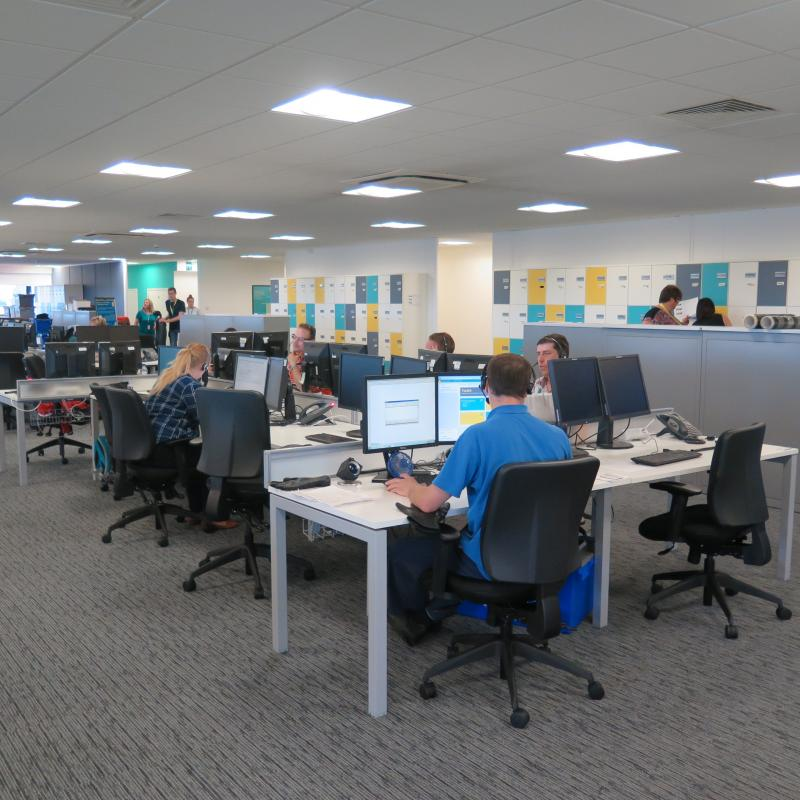 View of occupied banks of desks with coloured lockers beyond