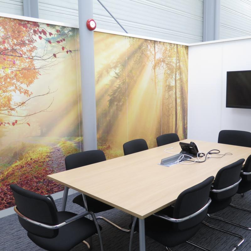 View of large meeting table, TV screen and back wall with photograph of autumn coloured tree scene and rays of sun shining through