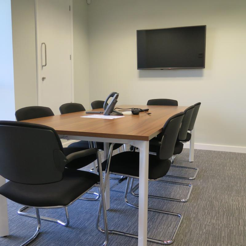 view of meeting room with table and chairs for 8 people and wall mounted TV