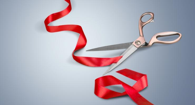 view of red ribbon having been cut by shiny scissors